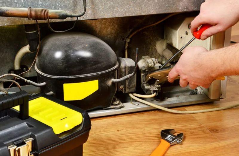 Мастер ремонтирует компрессор холодильника